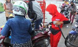 BBM NAIK : Petugas SPBU di Jalan Pakunegara, Pangkalan Bun, Kabupaten Kotawaringin Barat, mengisi premium ke tangki motor, Minggu (29/3). Pengumuman penaikan harga BBM yang mendadak membuat para pedagang eceran bingung dalam menetapkan harga.