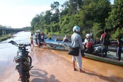 JASA PENYEBERANGAN: Sejumlah pengguna jalan terpaksa menggunakan jasa perahu getek untuk menyeberangi jalan yang kerap banjir di kilometer 30 jalan penghubung Pangkalan Bun-Kecamatan Kotawaringin Lama.