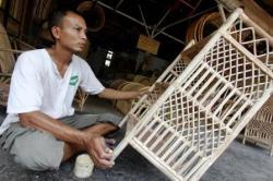 BEKERJA: Seorang pengrajin rotan menyelesaikan pekerjaan pembuatan furniture dari rotan di kiosnya di bilangan Jakarta Barat, Selasa (18/9). Sementara itu, untuk memperkuat permodalan para pengrajin rotan di Bartim, Pemkab menyalurkan bantuan modal melalui KUBE.