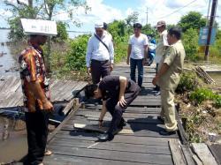 TITIAN ULIN RUSAK : Anggota DPRD Kapuas, Bob Dwi Cipta Mahaputera (tengah) meninjau kerusakan jalan titian ulin di Desa Murung Keramat, Kecamatan Selat, Kamis (16/4/2015)