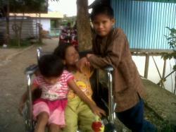 SANG ADIK: Muhammad, 14 (kanan), Norsa'adah, 12, dan Aminah, 10 (kiri) menggunakan kursi roda berfoto bersama di depan rumah, kemarin.