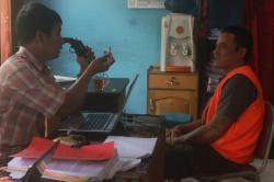 PENCURI CPO: Penyidik Polda Kalteng memegang pistol dan sebutir peluru yang disita dari Aang (kanan), tersangka ke-11 pencurian minyak sawit mentah (CPO) di Sampit.