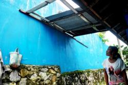 WASWAS : Sugiarti menunjukkan tembok pagar PT Delta Abadi Sentosa, Pangkalan Bun. Ia dan warga lainnya mengaku waswas dengan tembok beton yang kondisinya sudah retak-retak.