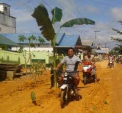 AKSI WARGA : Pengendara sepeda motor yang melintas di Jalan Suka Damai, Desa Kuayan, Kecamatan Parenggean, yang saat ini dalam keadaan rusak hingga ditanami masyarakat sekitar dengan pohon pisang, Jumat (24/4).