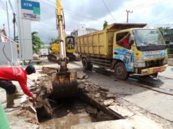 BONGKAR DRAINASE TERTUTUP : Salah seorang petugas drainase pada Dinas Pekerjaan Umum Kotim memandu alat berat yang membongkar drainase tertutup di Jalan HM Arsyad Sampit.