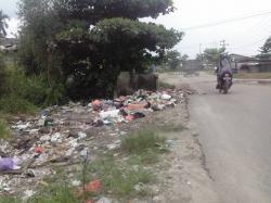 SAMPAH BERSERAKAN : Kondisi sampah yang berhamburan kemana-mana hingga memenuhi parit yang berada di sampingnya, hal itu terjadi karena TPS di Jl Kapten Mulyono tersebut rusak, Minggu (2/5/2015).