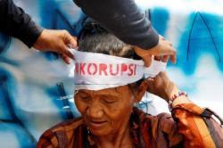 Seorang nenek memasang ikat kepala bertuliskan antikorupsi saat peringatan hari antikorupsi, beberapa waktu lalu.