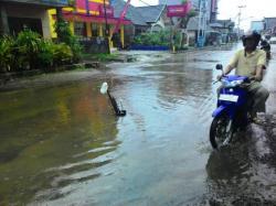 TERGENANG: Jalan Bahari Kumai, selalu tergenang usai hujan turun. Sementara di kala panas, jalur yang dilewati truk dan angkutan besar ini menjadi penuh debu.