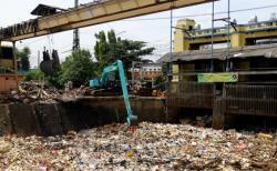 PINTU AIR : Sebuah alat berat sedang membersihkan sampah di pintu air Manggarai, Jakarta beberapa waktu lalu. Pemkab kotim mengusulkan pembuatan pintu air untuk mencegah banjir.