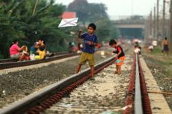 LAHAN BERMAIN ANAK: Sejumlah anak bermain di pinggir rel kereta api di kawasan Buaran, Jakarta Timur, Rabu (20/5). Minimnya lahan bermain dan Ruang Terbuka Hijau (RTH) di Jakarta membuat mereka harus bermain di daerah tidak layak dan berbahaya.