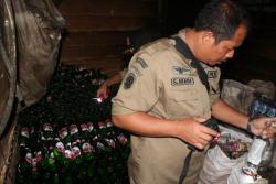 BOTOL BEKAS : Kepala Satpol PP Lamandau memperlihatkan botol Miras bekas yang disimpan di belakang THM.