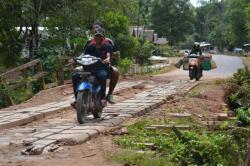 RUSAK: Warga melintasi jembatan di Desa Lupu, Kecamatan Balai Riam, Kabupaten Sukamara. Jembatan kondisinya cukup mengkhawatirkan. Meski bantalan lantai jembatan masih kuat namun karena jembatan tersebut tidak ada pagar pengaman di sisi kanan dan kiri dinilai warga rawan kecelakaan