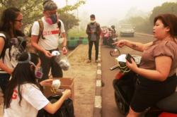 MINTA MASKER : Pengendara motor menghampiri warga Singapura Wolter Chia dan anggota Gerakan Let's Help Kalimantan untuk meminta masker yang memang dibagikan gratis di kawasan Universitas Palangka Raya, Kota Palangka Raya, Senin (5/10/2015).