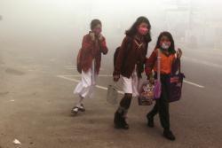 PAKAI MASKER : Tiga orang siswi SD berangkat sekolah di tengah kepungan kabut asap. Sementara itu, Pemkab Katingan memperpanjang status darurat asap di daerahnya.
