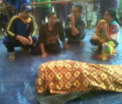 JENAZAH KOBAN : Dalam balutan kain sarung, salah satu jenazah korban yang hanyut di Sungai Katingan, disaksikan oleh keluarganya.