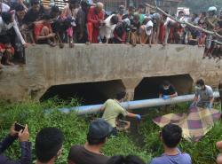 PENEMUAN MAYAT : Polisi dibantu warga mengangkat mayat wanita yang ditemukan membusuk di bawah Jembatan Jalan Pelita IV, RT 35 Kelurahan Buntok Kota, Minggu 911/10/2015).