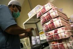 MENGHITUNG RUPIAH: Petugas menghitung tumpukan uang rupiah di Cash Center BNI, Jakarta, Rabu (1/4/2015). Rupiah terus menguat, menjauhi angka Rp13.500 per dolar AS.