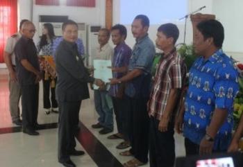 Bupati Lamandau Marukan tampak sedang menyerahkan sertifikat Prona kepada warga. Kepala BNP Lamandau Heri Mustain (paling kiri tertutup pejabat lain) turut hadir dalam acara itu.penyaksikan