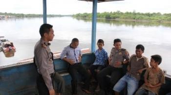 USAI menghentikan pencarian jasad bocah Ayu Lestari, yang tenggelam di Sungai Hanjalipan, Kapolsek Kota Besi Iptu M Syafuan (duduk di tengah), berbincang dengan warga di sebuah dermaga sungai, di Kecamatan Kota Besi, Jumat (5/2/2016). BORNEO/M HAMIM