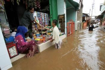 Warga beraktivitas saat banjir menggenangi kawasan permukiman. Banjir melanda sejumlah daerah di nusantara.