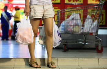 KANTONG PLASTIK: Warga membawa barang belanjaan dalam kantong plastik seusai berbelanja di salah satu toko modern, beberapa waktu lalu.