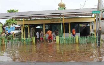 Sejumlah anak tengah bermain di depan musala yang terendam air akibat hujan. Beberapa wilayah di Kotim memang menjadi langganan banjir ketika hujan turun dengan intensitas tinggi. BORNEONEWS/Muhammad Rifqi