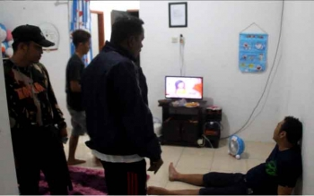 Roni duduk lemas saat digerebek belasan warga RT 18 Kelurahan Madurejo, Senin malam. BORNEONEWS/CECEP HERDI