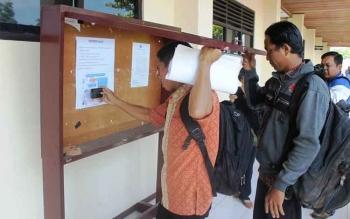 Para pelamar tenaga kontrak melihat pengumuman kelulusan yang ditempel di kantor BKD Kotim, beberapa waktu lalu.