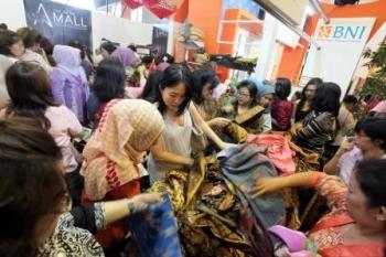 BEREBUT BATIK : Pengunjung berebut mendapatkan batik koleksi Designer Anne Avantie yang merupakan salah satu mitra binaan BNI pada pameran INACRAFT 2016 di Jakarta Convention Center (JCC), Jakarta, Kamis (21/4/2016). BNI merupakan salah satu bank yang men