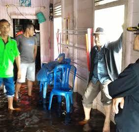Anggota DPRD Kapuas Robet L Gerung sedang berkomunikasi dengan warga Desa Tambak Bajai yang rumahnya terendam banjir. BORNEONEWS/DJEMMY NAPOLEON