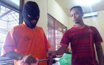 Billi Pasera didampingi penyidik reskrim Polsek Pahandut menunjukkan pukul yang ia gunakan membogem Harianti, Minggu (1/5/2016). BORNEONEWS/BUDI YULIANTO
