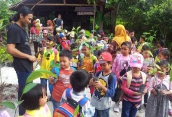Basuki sedang membagikan bibit pohon buah kepada anak-anak TK Bhayangkari.