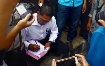 Manager Rayon PLN Pangkalan Bun Purwanto sedang menandatangani tuntutan massa dalam demo yang digelar 20 Maret 2016. DOK BORNEONEWS