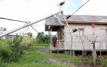 Husaini sedang menunjukkan tiang listrik yang tepat berada disamping rumahnya tertahan karena kabel listrik tersangkut di atap rumahnya. BORNEONEWS/NORNASANAH