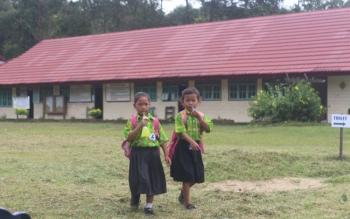PULANG SEKOLAH: Dua murid SDN Tamiang saat pulang sekolah. Wakil Ketua DPRD Lamandau, FX. Perwiragato menilai perda perlindungan anak patut diwacanakan. BORNEO/HENDI NURFALAH