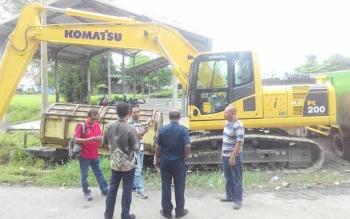 ALAT BERAT: Alat Berat milik Dinas PU Kabupaten Kapuas dibobol maling. Awak media berbincang dengan petugas keamanan di area Jalan workshop Jalan Patih Rumbih Kamis (19/5/2016) siang. BORNEO/DJEMMY NAPOLEON
