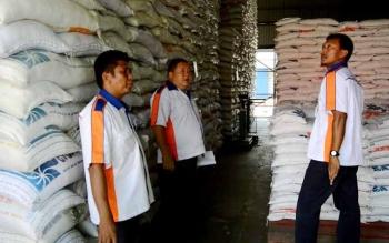 Sejumlah petugas Bulok sedang melakukan pemeriksaan terhadap beras yang mereka simpan di dalam gudang. Attachments area