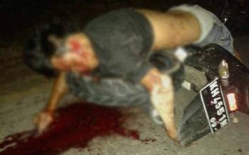 KORBAN KECELAKAAN: Arab (31) warga Tumbang Atei Kecamatan Sanaman Mantikei tertelungkup di atas sepeda motornya. Arab tewas ditempat setelah sepeda motornya menghantam gundukan pasir dan kemudian tubuhnya terlindas sepeda motor.borneo/Ist/abdul gofur