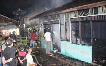 Sejumlah petugas damkar dan warga sedang berusaha memadamkan api yang membakar sebuah rumah dan barak tiga pintu di Jl Usman Harun, Kecamatan Baamang, jumat (24/6/2016). BORNEO/HAMIM