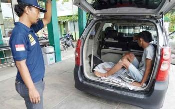 Seorang anggota Polsek Ketapang sedang menunggu pelaku jambret keluar dari mobil, saat dibawa ke rumah sakit untuk melepaskan peluru yang bersarang di kakinya. BORNEONEWS/HAMIM