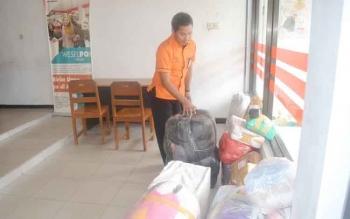 Kepala Kantor Pos Sukamara, Ngadimin sedang mencek paket kiriman yang baru tiba. BORNEONEWS/NORHASANAH