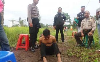 Sejumlah anggota Polsek Ketapang sedang berdiri di belakang tersangka maling walet yang mereka tangkap bersama warga beberapa waktu lalu. BORNEONEWS/HAMIM
