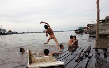 Sejumlah anak terlihat begitu menikmati bermain di bantaran Sungai Mentaya. Sebagai pemilik masa depan anak-anak harus dijamin hak-haknya. BORNEONEWS/M.RIFQI