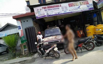 Seorang pemuda yang belum diketahui identitasnya, dalam kondisi telanjang bulat mengendarai sepeda motor dan berjalan kaki di Jalan Raya, Kota Kasongan, Jumat (29/7/2016). BORNEONEWS/PPOST/HAIRUL SALEH