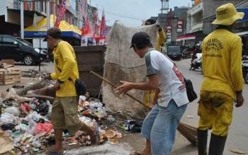 Sejumlah petugas kebersihan membersihkan tumpukan sampah di depan Pasar Mangkikit, Jalan Pangeran Antasari, Kotawaringin Timur, beberapa waktu lalu. BORNEONEWS/M.RIFQI