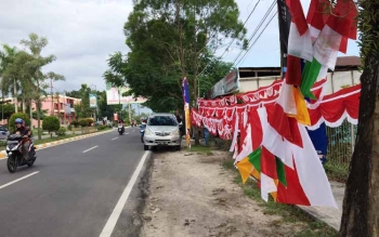 Pengendara sepeda motor melintas di depan atribut HUT kemerdekaan yang dijual pedagang di pinggir jalan Iskandar, Pangkalan Bun, Jumat (29/7/2016). BORNEONEWS/CECEP HERDI