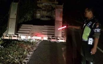 Seorang anggota menunjukan titik dimana mobil Avanza menabrak bagian belakang sebelah kanan truk trailer, Rabu (24/8/2016). BORNEONEWS/BUDI YULIANTO