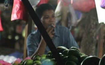 Seorang pedagang buah di Kuala Pembuang, tengah menikmati isapan rokoknya sambil menunggu kedatangan pembeli. BORNEONEWS/PARNEN