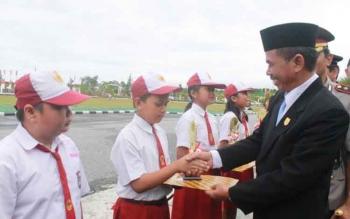 Ketua DPRD Gunung Mas Gumer memberikan penghargaan kepada para pelajar berprestasi, beberapa waktu lalu. Gumber menyesalkan terjadinya kasus penganiayaan terhadap guru, yang dilakukan oknum ASN. BORNEONEWS/EPRA SENTOSA