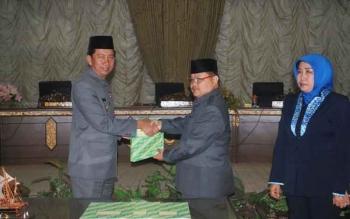 Bupati Barito Utara, H Nadalsyah (kiri) menyerahkan materi sidang Raperda pertanggungjawaban APBD tahun anggaran 2015 kepada Ketua DPRD Set Enus Y Mebas, Jumat (26/8/2016). BORNEONEWS/PPOST/AGUS SIDIK